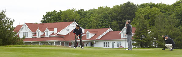 Event photography THCF golf tournament golfer putting on green with clubhouse in background