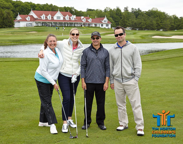 Event photography THCF annual invitational golf tournament golfers posing for picture with pond