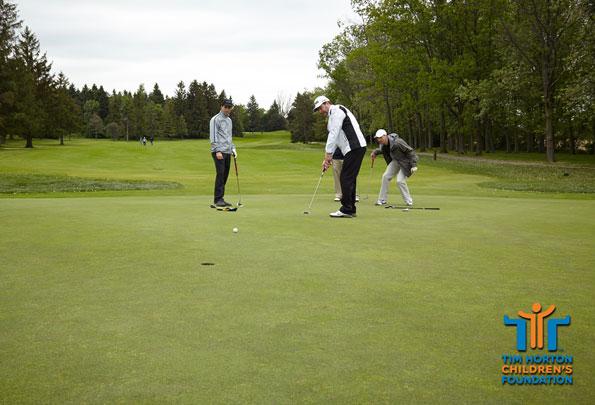 Event photography Tim Hortons golf tournament golfers putting on green